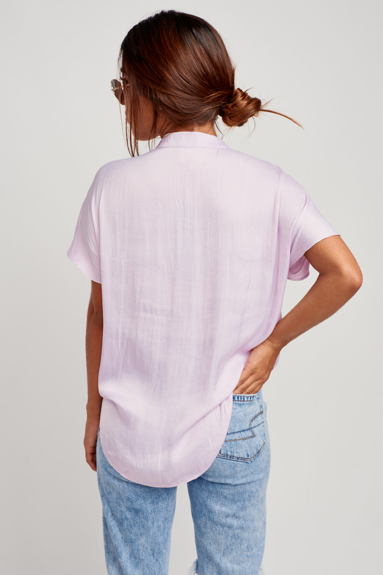 This lavender-colored blouse has a banded collar and v-neckline, short sleeves, and a relaxed bodice. Keep it versatile for the day by pairing it with jeans.