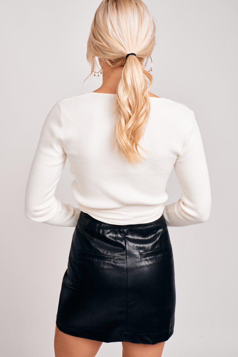 Long knit and ribbed sleeves attached to a deep v-neckline with a fitted and cropped bodice goes into a banded waistline with a tie front hem.