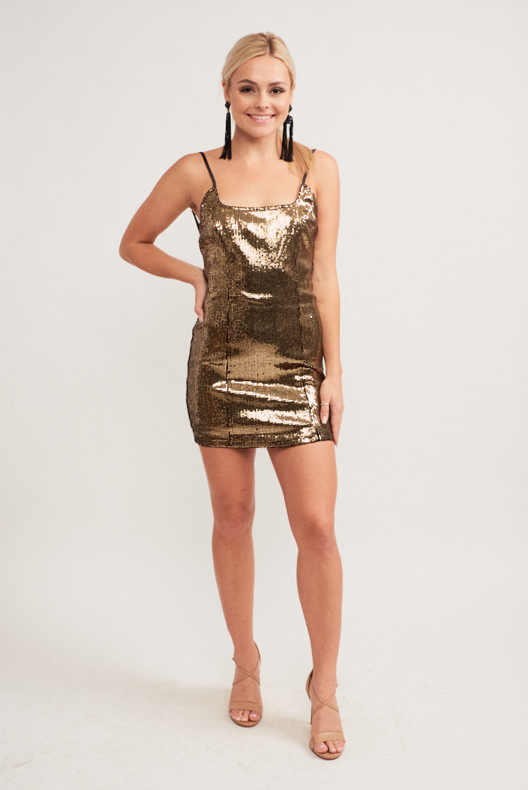 Mini gold sequins embellish this dress. Thin adjustable straps attach to a square neckline and lead to a fitted bodice and mini skirt dress that is princess-darted.