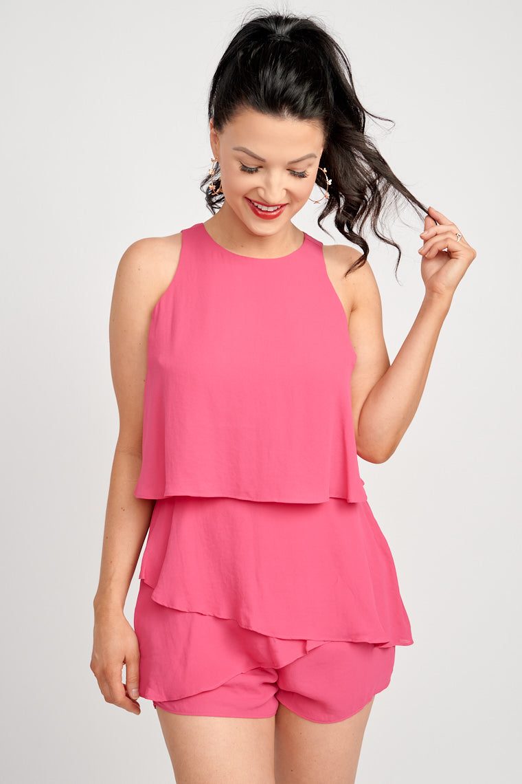 Medium straps on a high-neckline flounce bodice leading to a fitted waistband with tiered ruffles atop of relaxed shorts. This romper features a zipper to secure down the back.