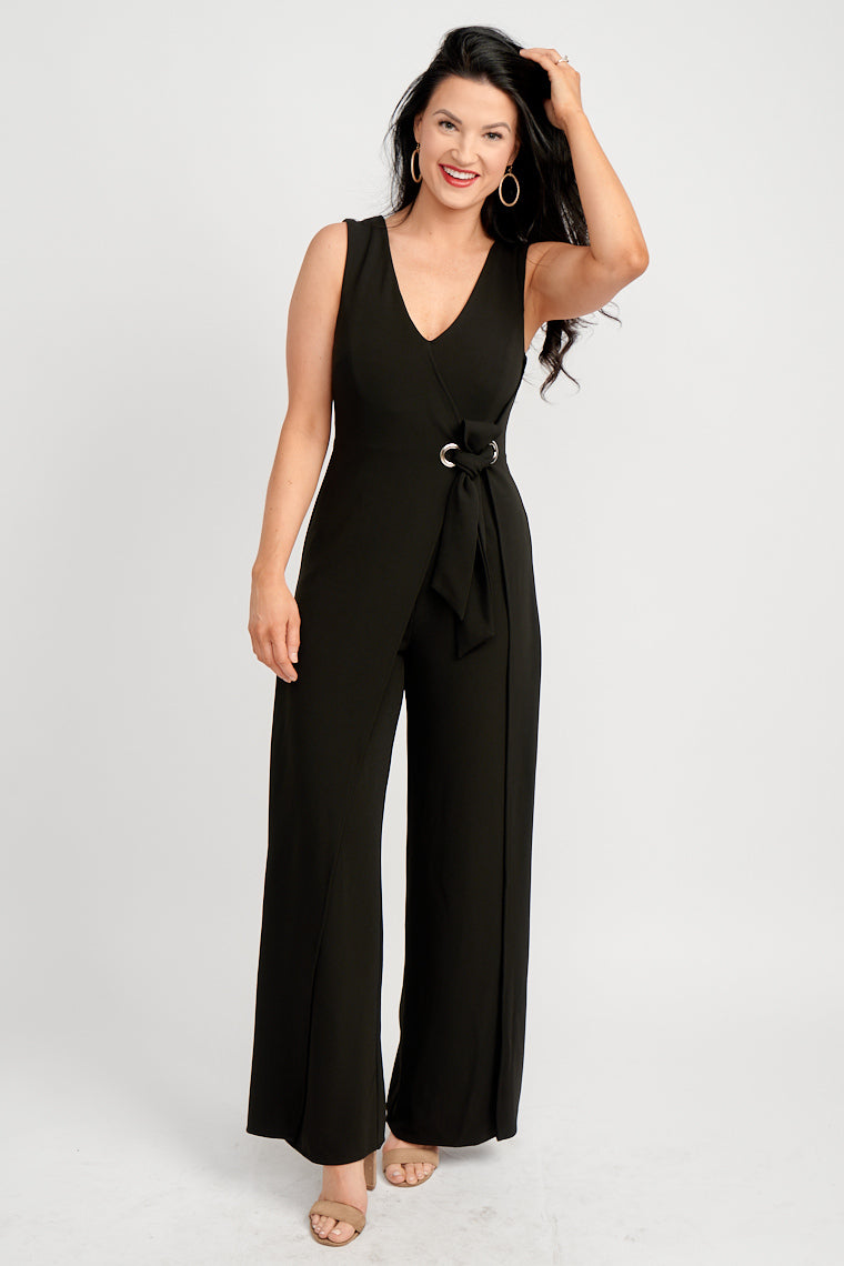 Medium straps attach to a surplice neckline on a fitted and darted bodice, fitted waist with grommet details at the side with a fabric tie and flows down to wide pant legs