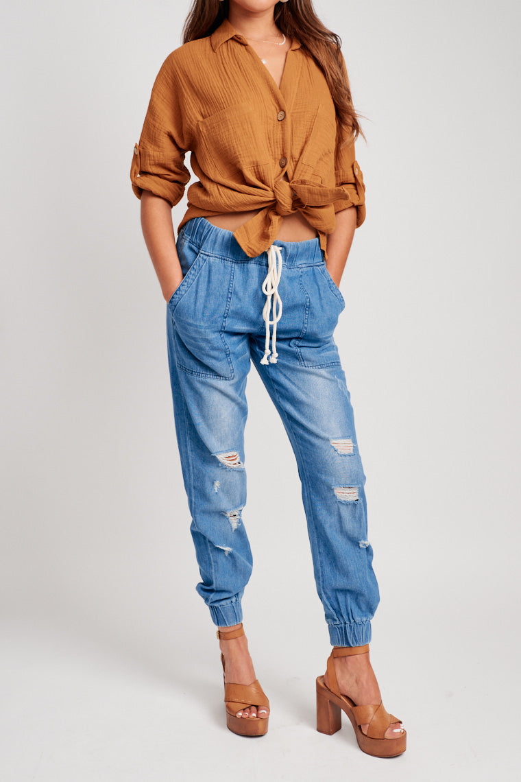 An elastic waistband with a contrasting white drawstring leads to square front pockets and faded wash pant legs with gentle distresses and cuffs at the ankle.