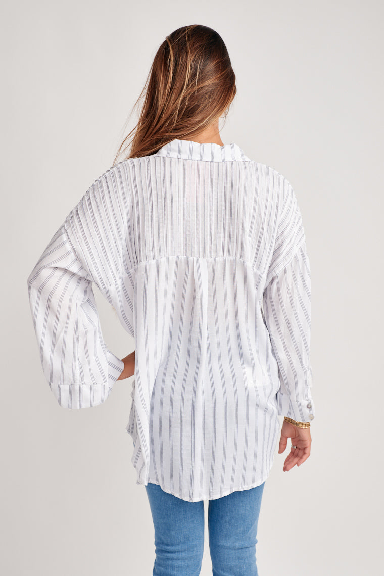This lightweight, blouse is decorated by navy pinstripes on the white background. The collared neckline, button-down an over-sized silhouette with long sleeve.