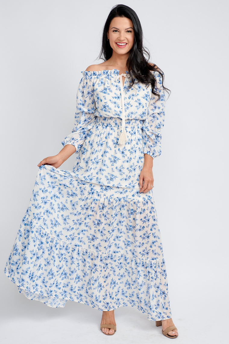 Mid-length puffed and ruched sleeves attach to a ruffled split neckline with a tassel drawstring, relaxed bodice silhouette, tiered and flowy maxi skirt.
