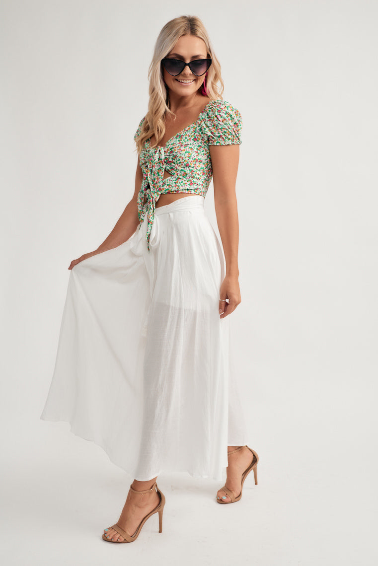 This lightweight, white maxi skirt offers a high-rise banded waistline with a tie front feature and a skater midi skirt silhouette.