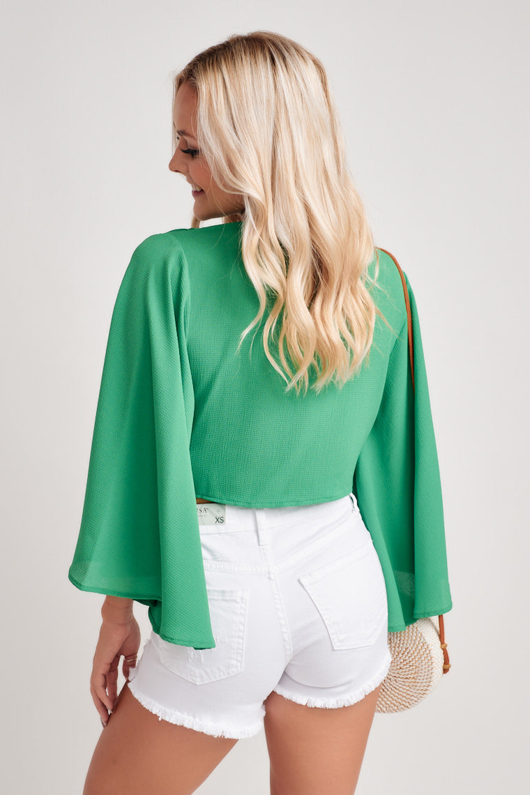 Gorgeous green crop top with a plunging neckline and a tie front feature. The long bell sleeves add some dramatic flair to finish off the number.