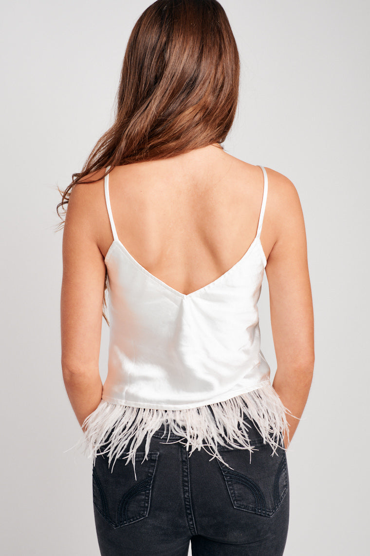 This satin tank has thin straps that attach to a v-neckline and relaxed darted bodice. The hem of the tank is detailed by wispy blush feathers that add a trendy finish.