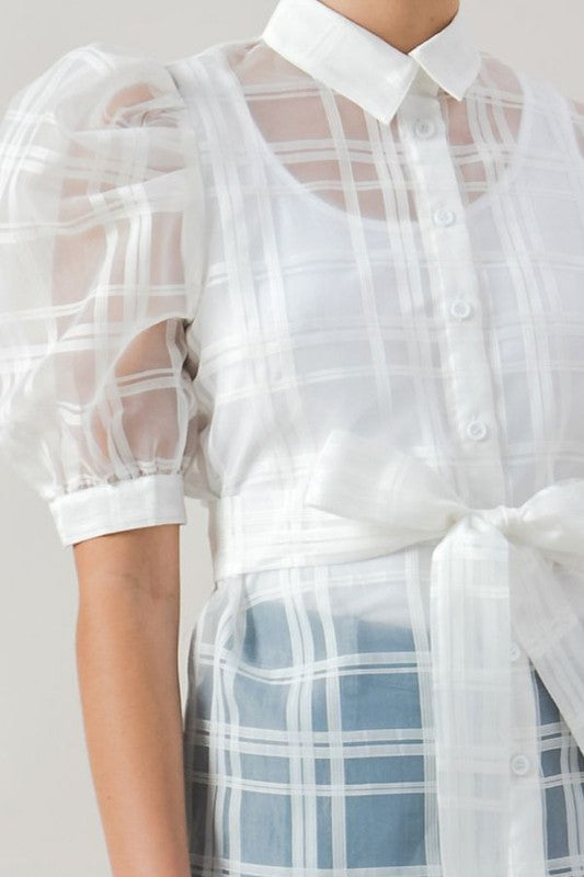 This sheer plaid printed top has mid-length banded puff sleeves that attach to a collared neckline and lead down to a fitted button-down bodice.