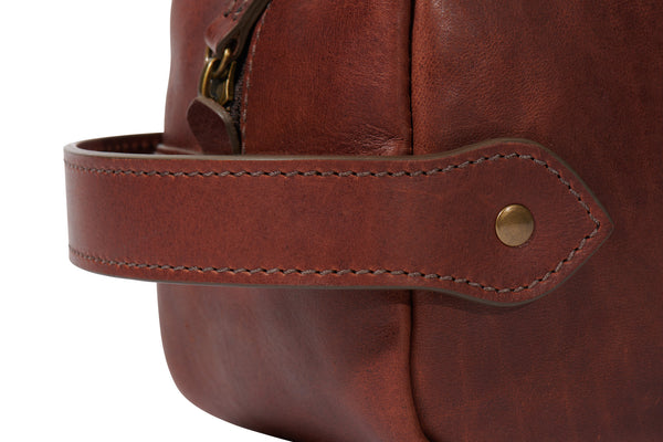 close detail of full grain leather Dopp kit handle in vintage brown color