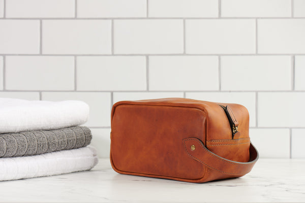 main view of Jackson Wayne full grain leather Dopp kit toiletry bag pictured in saddle tan color bathroom background