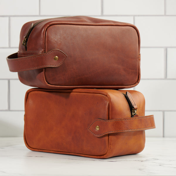 Jackson Wayne full grain leather Dopp kit toiletry bag in two colors: vintage brown and saddle tan bathroom tile background