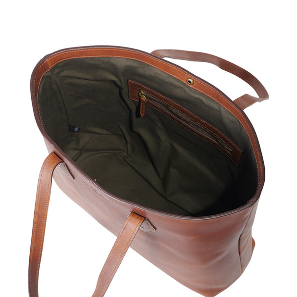 inside of Jackson Wayne leather tote bag in wildwood brown color with interior zipper pocket and snap closure