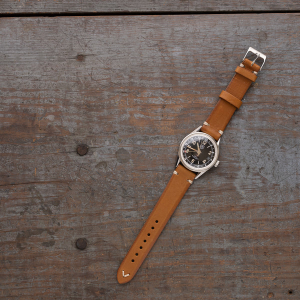vintage leather watch band made of full grain Italian leather with black watch pictured in saddle tan color and stainless steel buckle