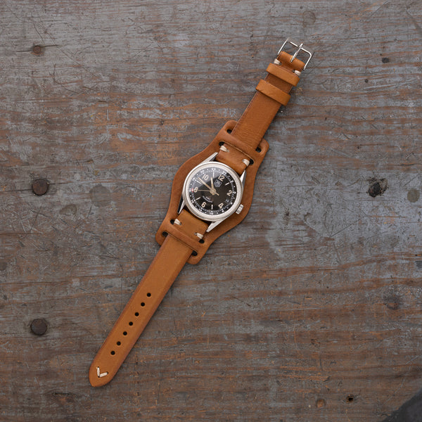 vintage Italian leather watch strap with bund pad by Jackson Wayne, pictured in saddle tan color with black watch