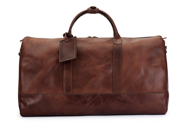 saddle tan full grain leather weekender bag with luggage tag in vintage brown