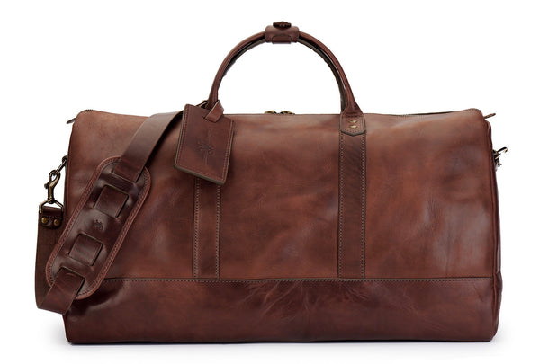 saddle tan full grain leather weekender bag with luggage tag in vintage brown and shoulder strap