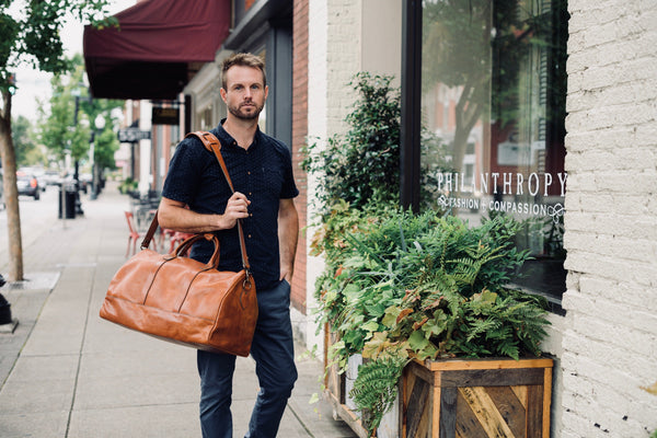 Jackson Wayne Big Sur Duffle Bag lifestyle shot in saddle tan walking on street with shoulder strap - full grain leather