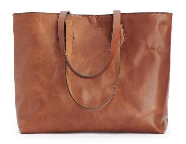 full grain leather tote bag travel carryall bag with solid brass hardware pictured in saddle tan leather