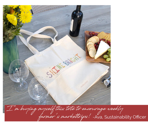 Printed cotton tote bag laying on table with flowers, wine, and cheese platter.