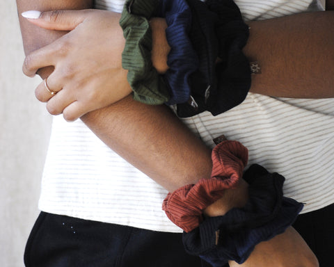 Close up of hand on arm with ribbed scrunchies stacked on wrists