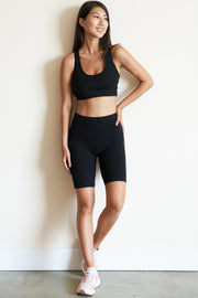 Full front view of model wearing black ribbed bike shorts.