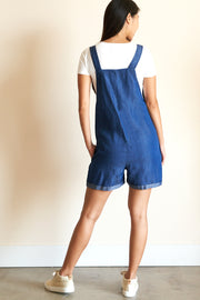 Full back view of model wearing denim overall and white tee.