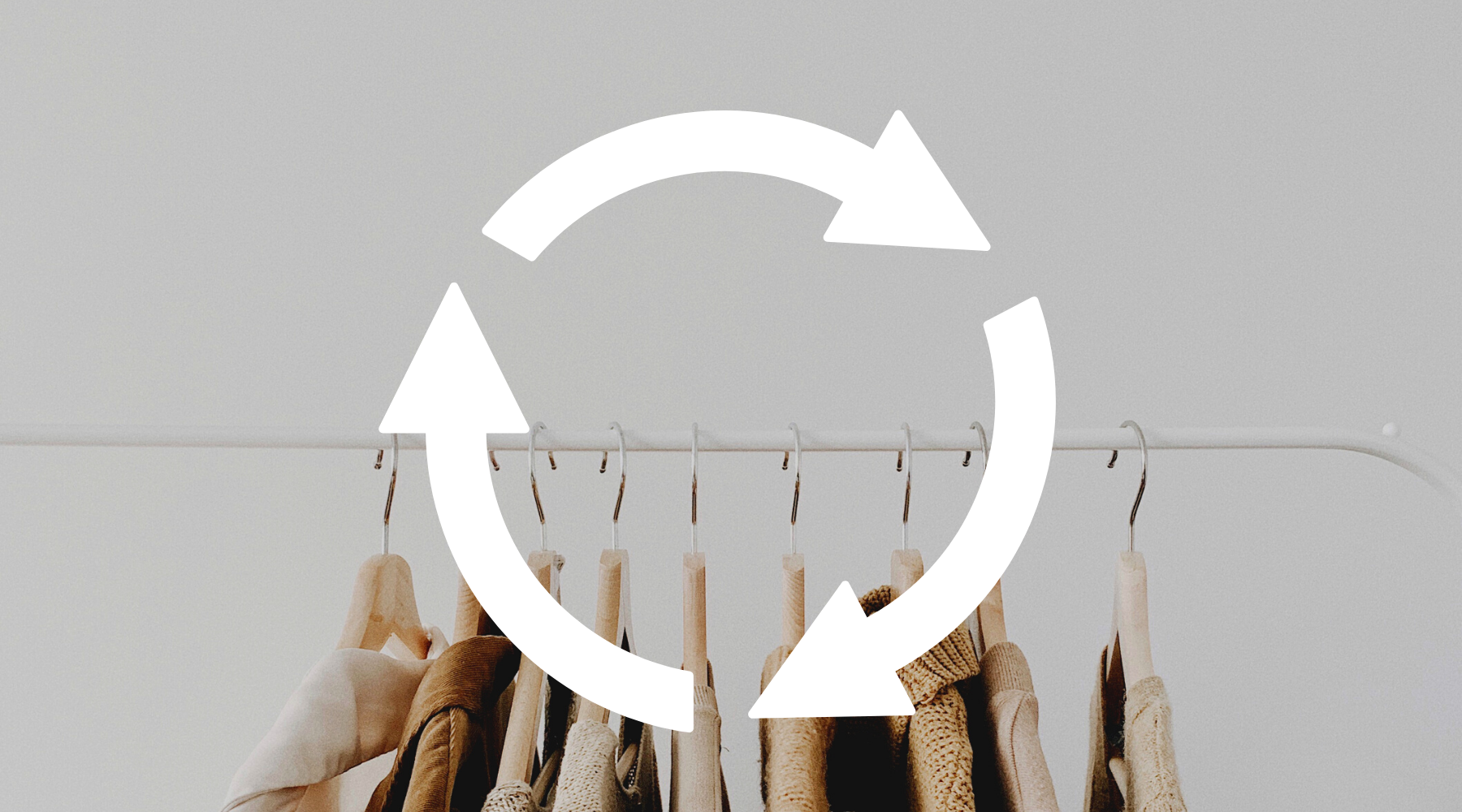 clothing rack with clothing on it, with recycling sign laid over top