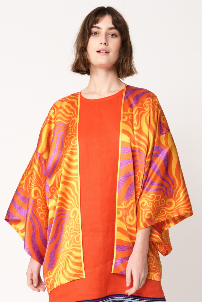 woman wearing flowy drapey orange and purple silk printed jacket over orange dress