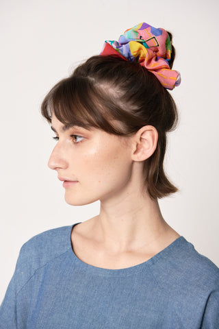 woman wearing blue and pink silk printed retro scrunchie in her hair