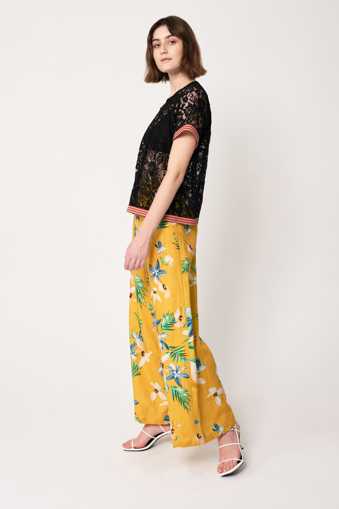 woman wearing black floral lace with pink ribbing on top of yellow wide leg pants