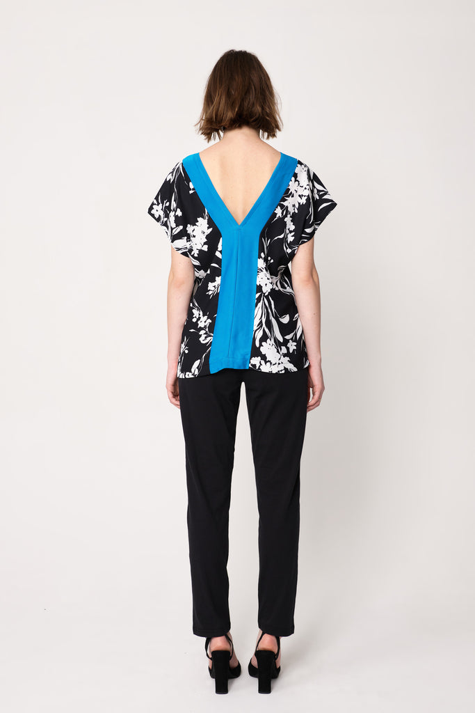 woman wearing black and white floral top with blue border around neck and sleeves