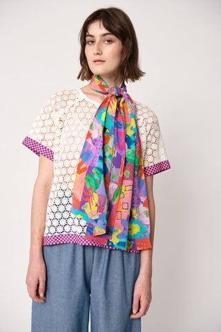 woman wearing blue and pink silk printed rectangular scarf tied around her neck with fun print