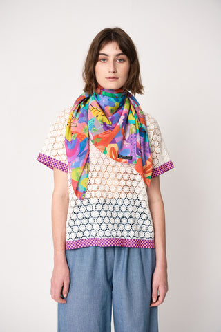 woman wearing blue and pink silk printed square scarf over white lace top with wide blue trousers