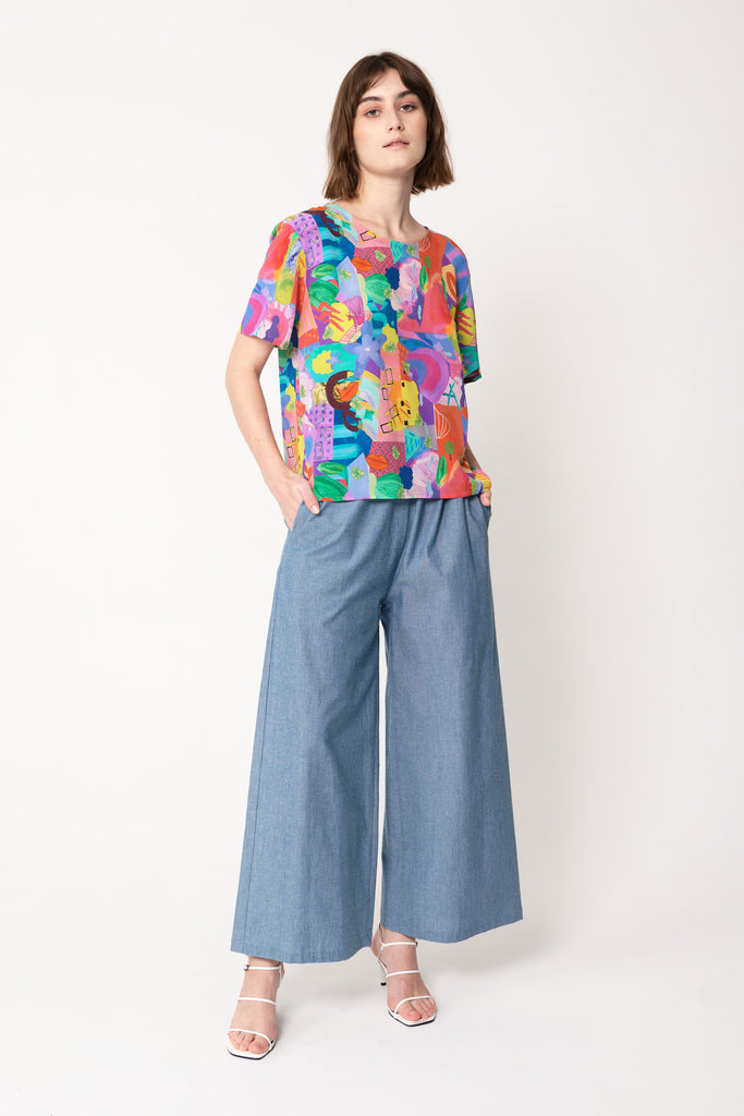 woman wearing blue and pink silk printed t-shirt with fun print over blue wide trousers