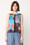 woman wearing blue red and black silk shell top with enlarged heart paisley and splice down centre