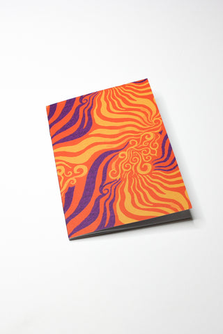 orange and purple printed notebook laying flat on white background