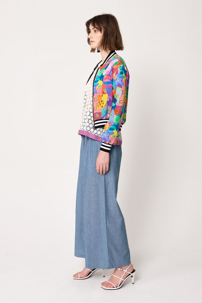 woman wearing blue and pink silk printed bomber jacket with varsity ribbing over lace top with blue wide-leg trousers