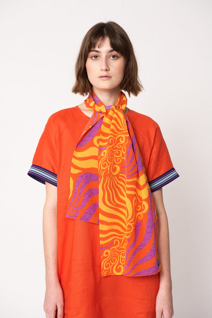 woman wearing orange and purple silk printed rectangular scarf tied around her neck on top of orange dress