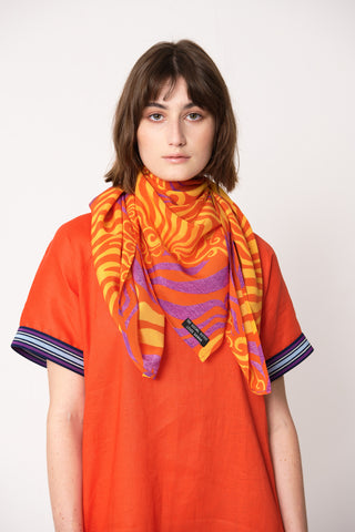 woman wearing orange and purple silk printed square scarf tied around her neck on top of orange dress