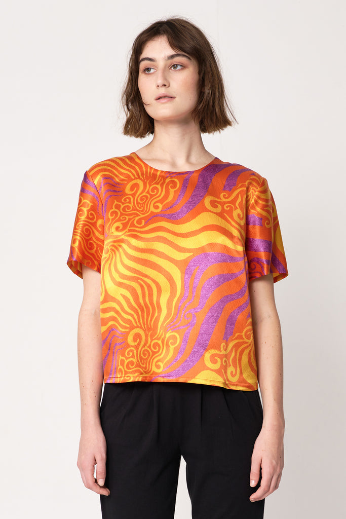 woman wearing orange and purple silk printed t-shirt with sleeves on top of black straight-leg pants and heels