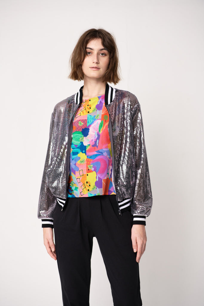 woman wearing sequin bomber jacket with cotton accent rib over colourful silk print tee and black straight leg pants