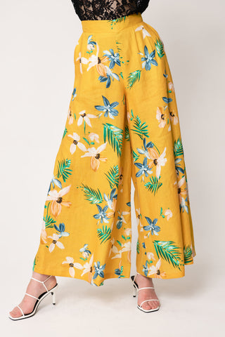 woman wearing yellow floral wide leg palazzo pants with black lace top tucked in