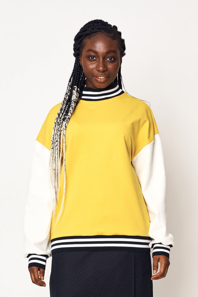 Henrietta wears our White Sleeve Bumblebee Pullover with our Noir Weave Wrap Skirt for AW21 Earth to Sky