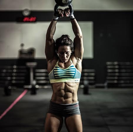 Strong woman swinging kettle bells at crossfit gym