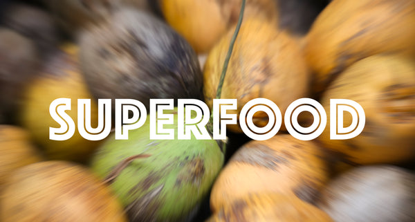 Blurry raw coconut background with 'superfood' font in foreground