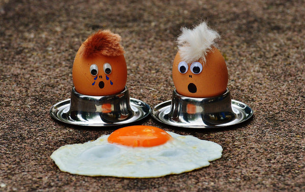 Eggs with cartoon faces grieving loss of fried egg on concrete