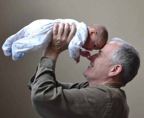 Grandfather in green shirt holding up baby in white bodysuit