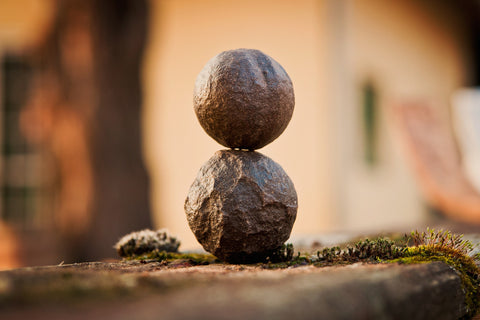 two round stone balls balancing on top of each other