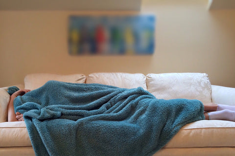 Man sleeping on couch with blanket over his head during the day