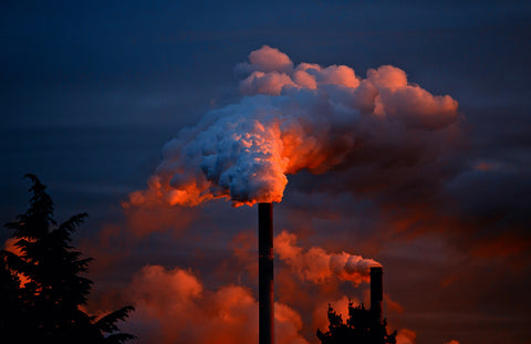 Industrial factory billowing smoke into the air at dusk